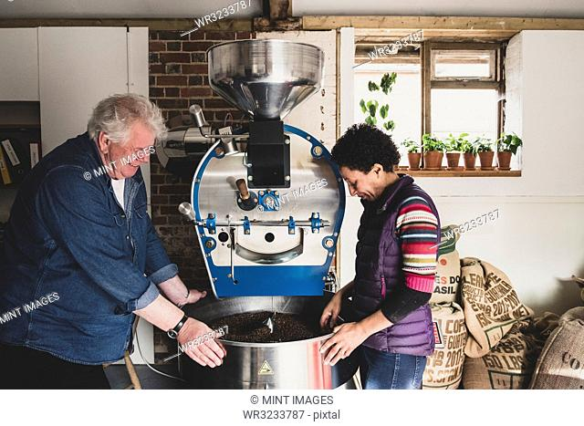 Man and woman standing next to coffee roaster, checking coffee beans