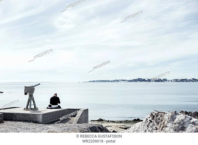 Rear view of man sitting by telescope overlooking sea against sky