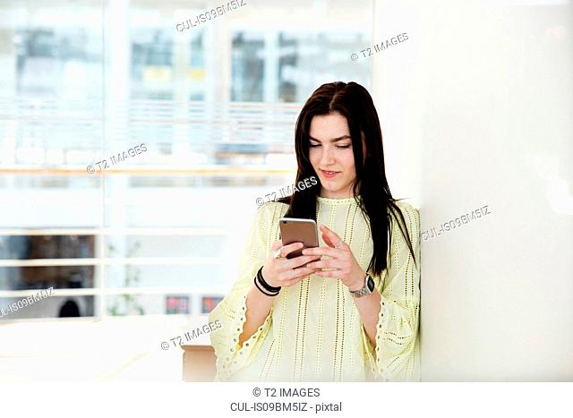 High school girl in school lobby looking at smartphone