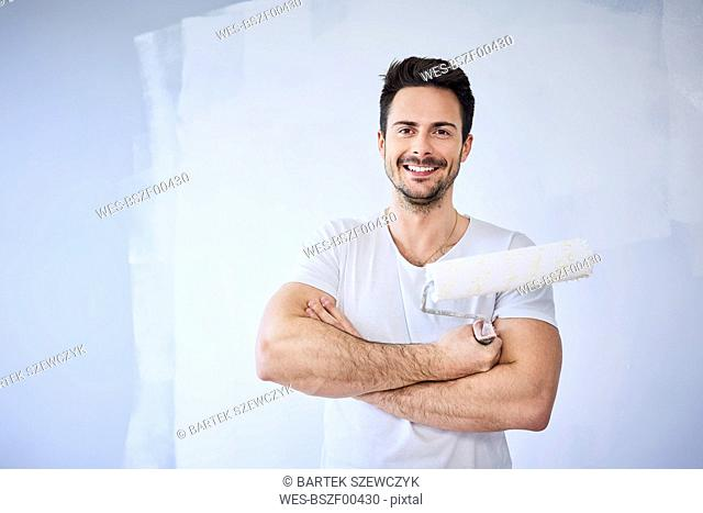 Portrait of smiling man painting wall in apartment