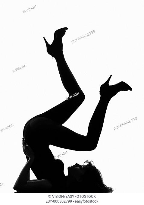 full length silhouette in shadow of a young woman floor gymnastic pike position legs in studio on white background isolated