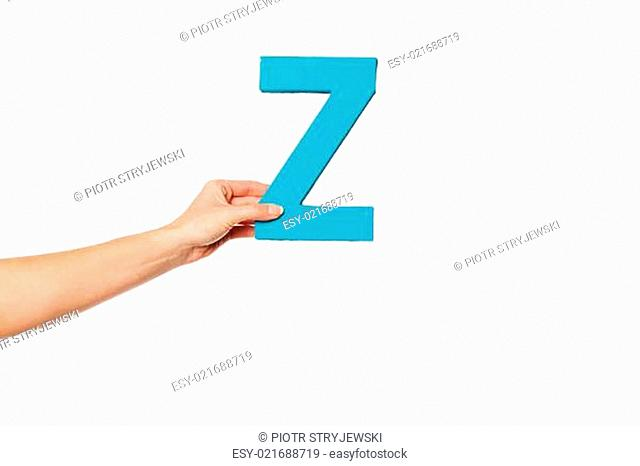 hand holding up the letter Z from the left