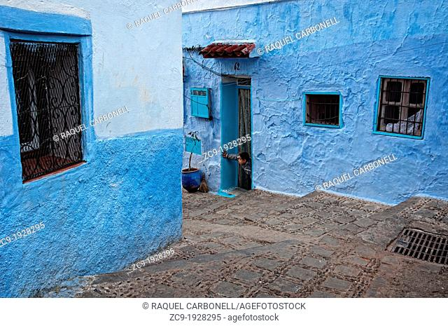 Boy at the door of his house in the blue medina de Chefchaouen Morocco