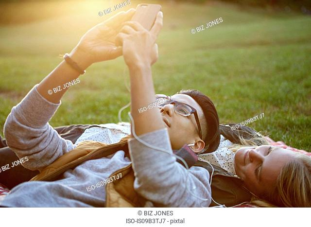 Couple on picnic blanket in park sharing earphone music