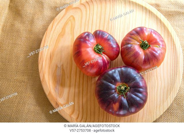 Three blue sea tomatoes on wooden dish. Still life