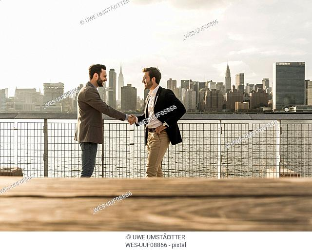 USA, New York City, two businessmen shaking hands at East River