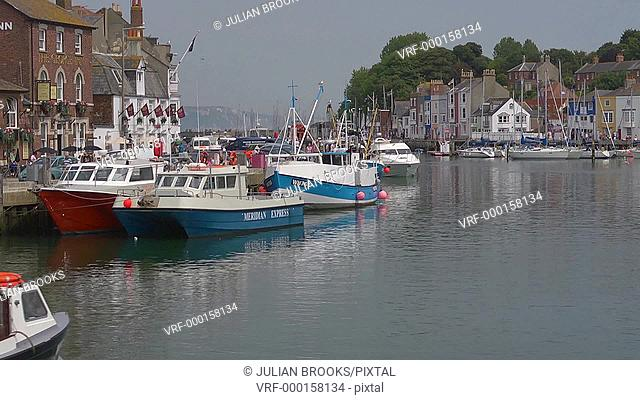 The old harbour and waterfront at Weymouth. Fishing boat going past