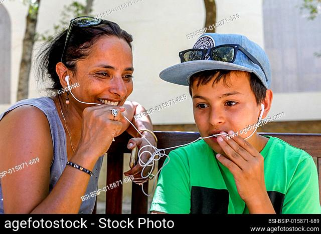 Mother and son having a cell phone conversation and sharing earphones in Sicily (Italy)