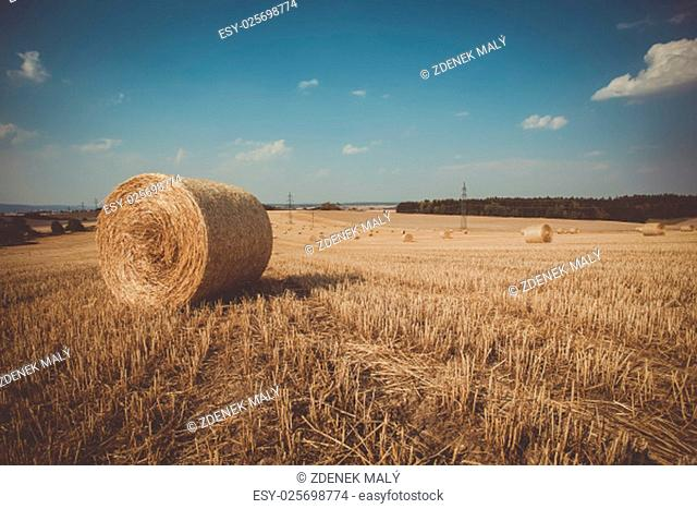 Beautiful landscape with straw bales in harvested fields, Czech Republic, Vysocina with blue sky and clouds, retro color