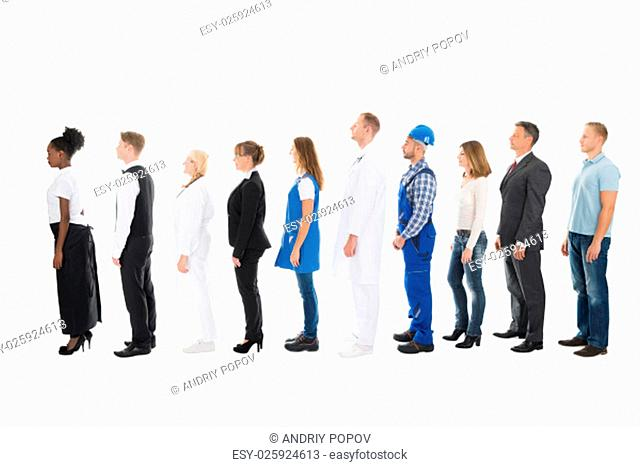 Full length side view of people with various occupations standing in queue against white background