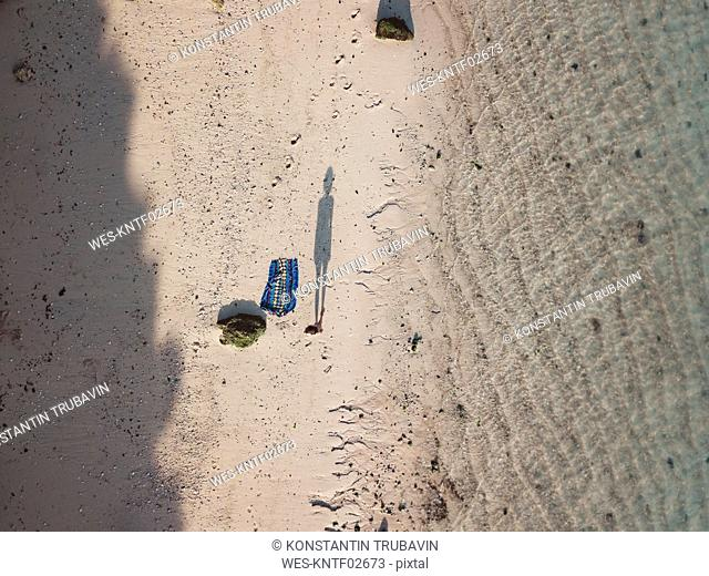 Shadow of woman standing on the beach, top view