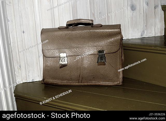 An old leather briefcase is standing on a staircase. An old leather briefcase is standing on a staircase