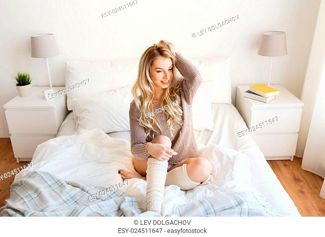rest, sleeping, comfort and people concept - happy young woman posing in bed at home bedroom