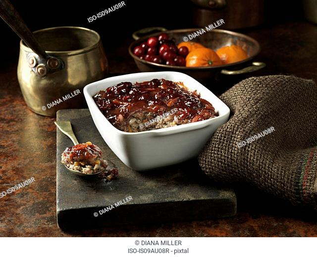 Roasted pork with cranberry and mandarin stuffing on rustic chopping board