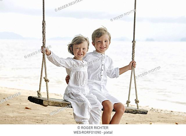 Thailand, Ko Yao Noi, portrait of smiling boy and little girl on a swing on the beach