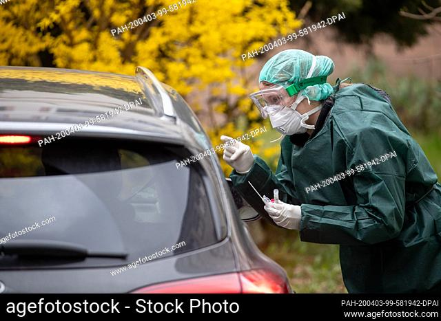 03 April 2020, Bavaria, Nuremberg: An employee of the public health department takes a smear in a corona test centre from a person in his car
