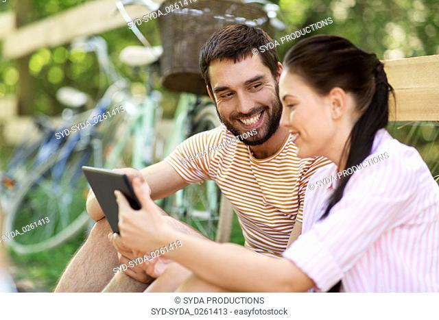 couple with tablet pc and bicycles at summer park
