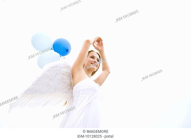 Young woman wearing angel wings holding balloons, smiling, portrait
