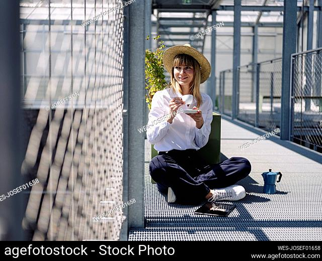 Businesswoman wearing hat with coffee cup sitting by fence in greenhouse