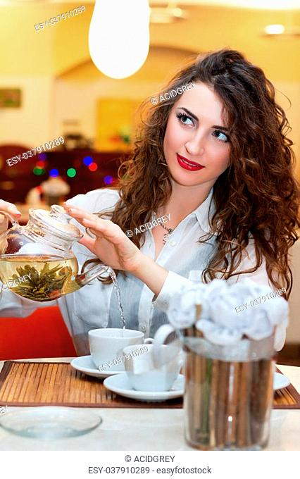 Pretty young woman pours tea into a cup