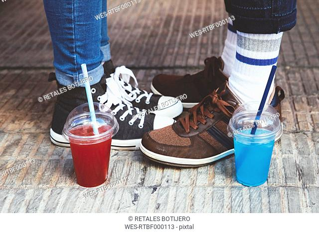 Plastic cups with soft drinks standing besides feet of young couple