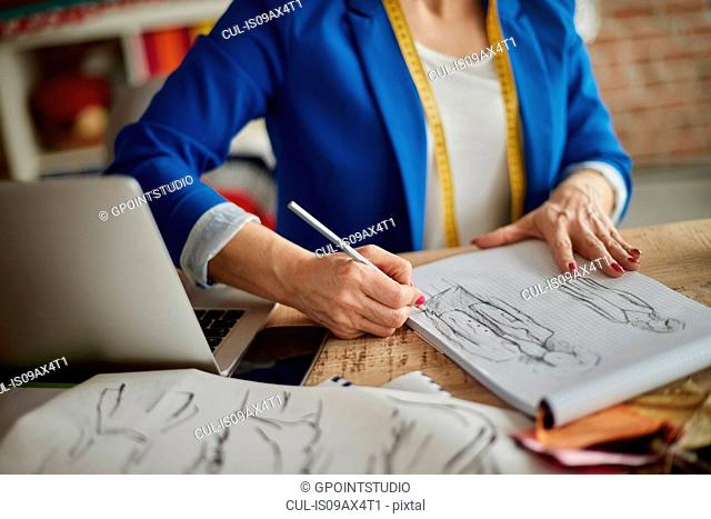 Cropped view of woman sitting at desk sketching fashion design