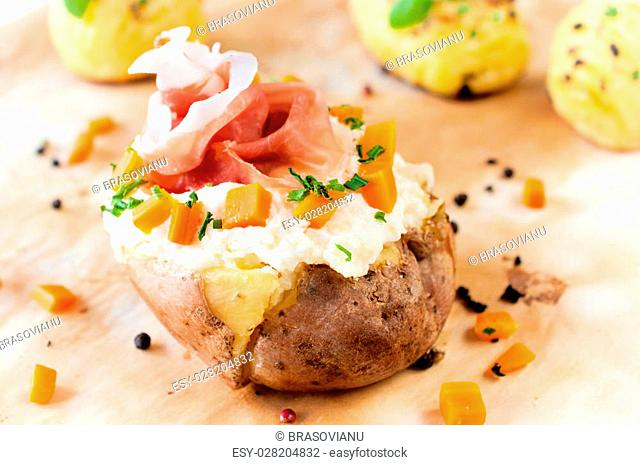 Fresh baked potato and prusciutto with white cheese cream