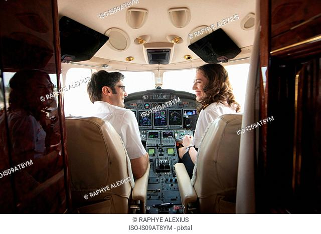 Rear view of male and female pilot chatting in cockpit of private jet
