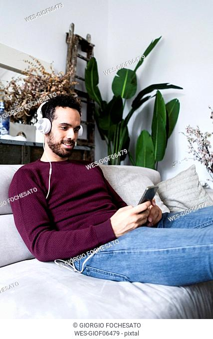 Smiling man sitting on couch with cell phone and headphones