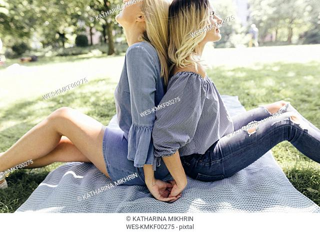 Two young women sitting back to back on a blanket in a park