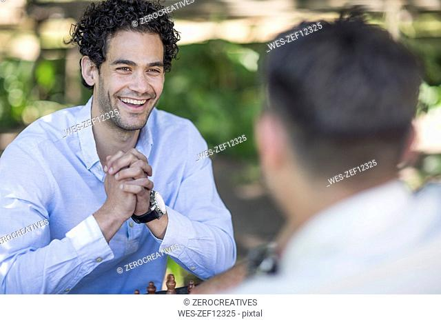 Happy young man playing game of chess in park