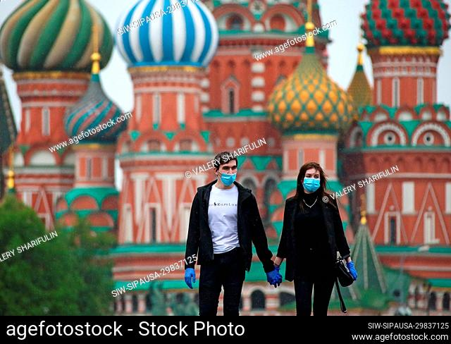 MOSCOW, RUSSIA - MAY 12, 2020: Young people hold hands as they walk in central Moscow. Moscow Mayor Sergei Sobyanin made mandatory wearing face masks and gloves...