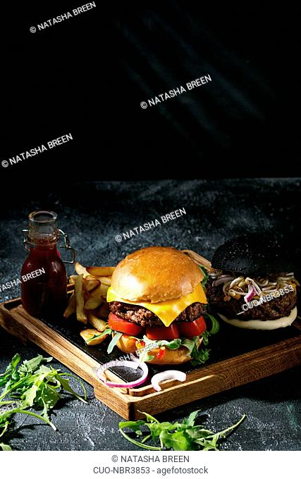 Homemade black and white buns hamburgers with beef, mozzarella cheese, sprouts, arugula, served on wooden slate serving board with french fries and ketchup...