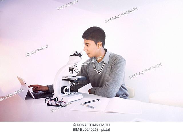 Fiji Indian boy using digital tablet and microscope