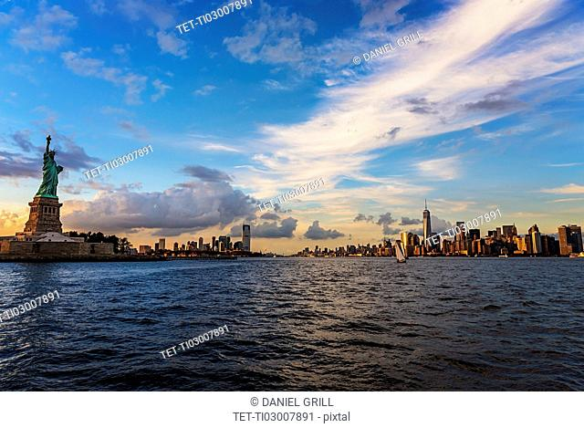 Statue of Liberty and financial district at dusk
