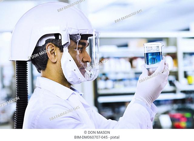 Indian male scientist wearing respirator and looking at beaker