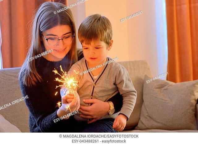 Little boy and teen girl holding a sparkler inside of house