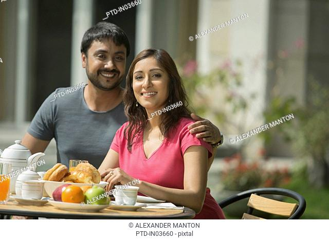 Man with arm around woman at breakfast table outside