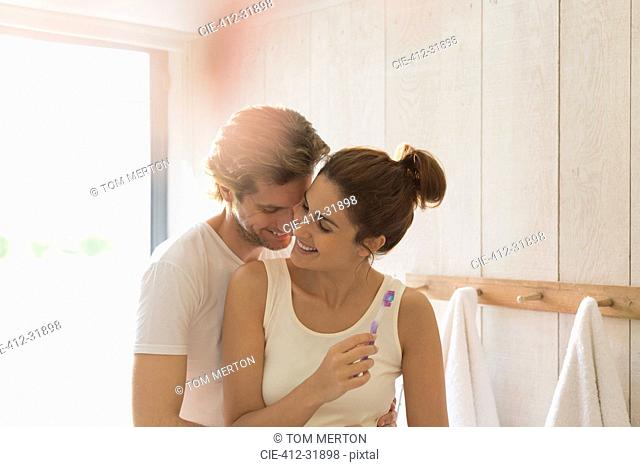 Affectionate couple brushing teeth in sunny bathroom
