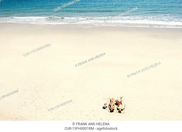 Couple sunbathing on white sandy beach