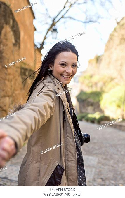 Happy young woman holding hand of boyfriend