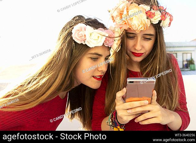 Two young girls with red dress and long blonde hair and roses looking a selfie