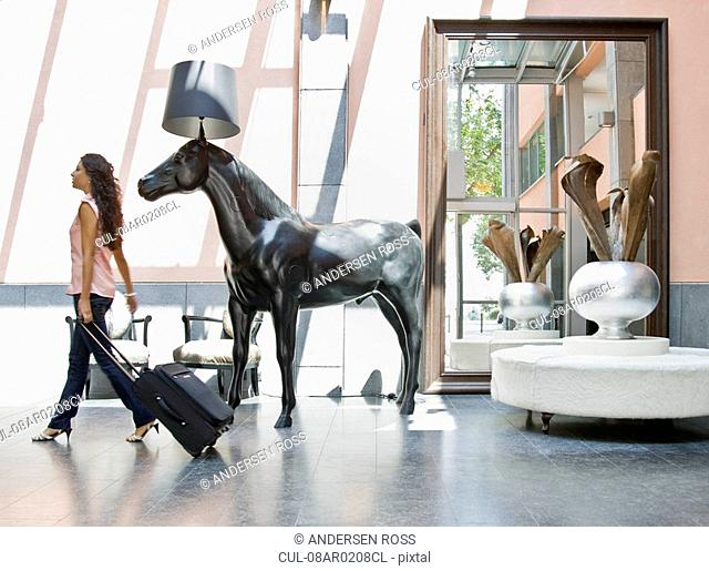 Woman with luggage in a lobby