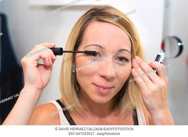 Beautiful blonde woman applying mascara on her eyelashes
