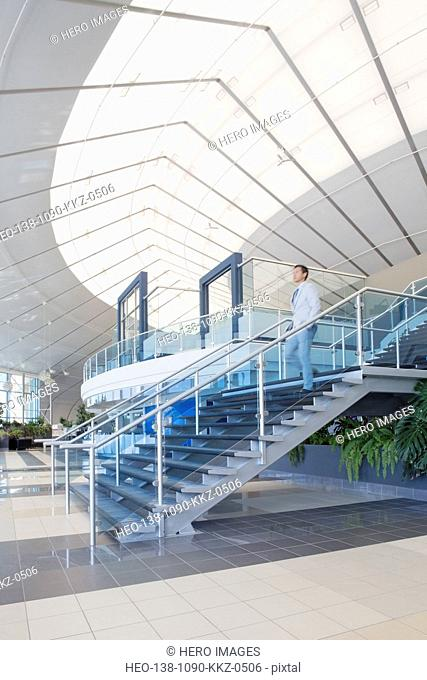 Businessman descending modern staircase in office atrium