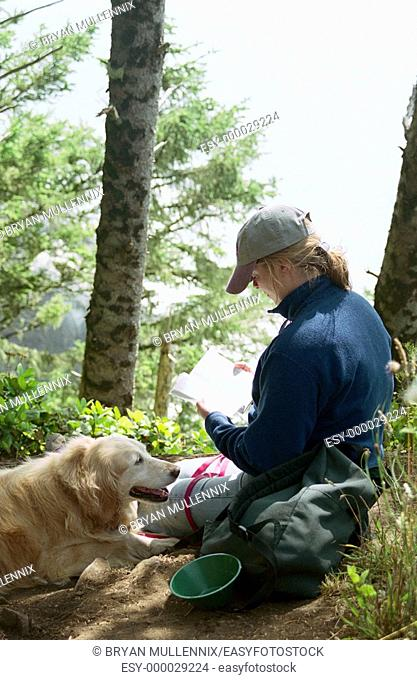 34 year old woman reading book in forest with Golden Retriever. Oregon, USA