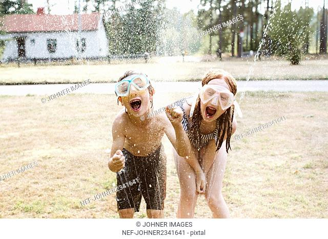 Cheerful kids playing with water