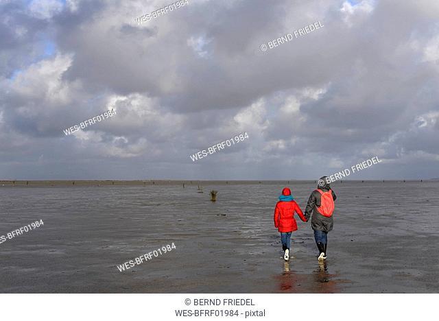 Germany, Lower Saxony, North Sea,   Hamburg Wadden Sea National Park, Neuwerk, low tide, mother and daughter walking in mudflat