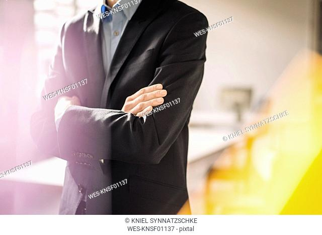 Businessman with arms crossed wearing black jacket, partial view