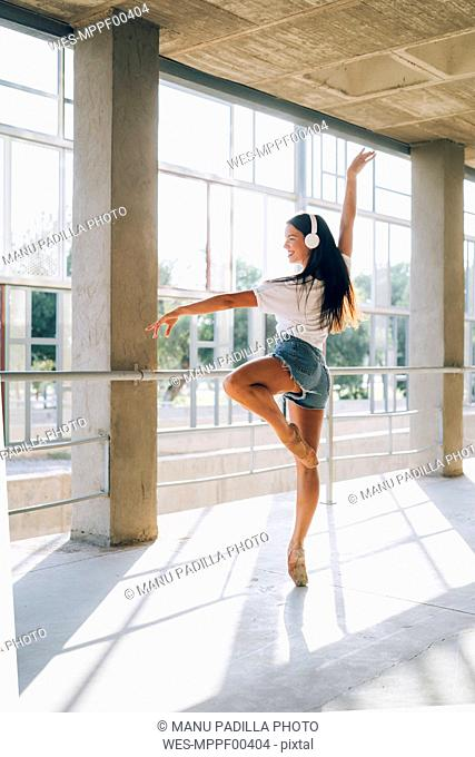 Ballerina with headphone dancing in gym